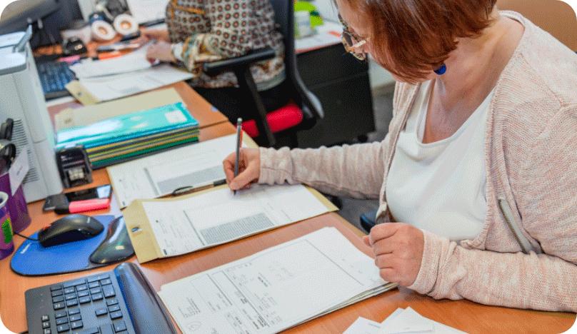 Une collaboratrice en train de vérifier les notes de frais pour le traitement comptable.